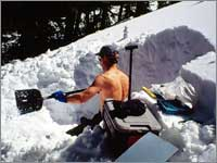Worker prepares snowpit on warm day at site near Deadman Pass, Colo.